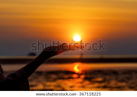 Silhouette of a woman's hand, holding sea shell against the setting sun on the seashore. Sun presented as a shiny pearl. Beautiful sunset picture on vacation in Asia.