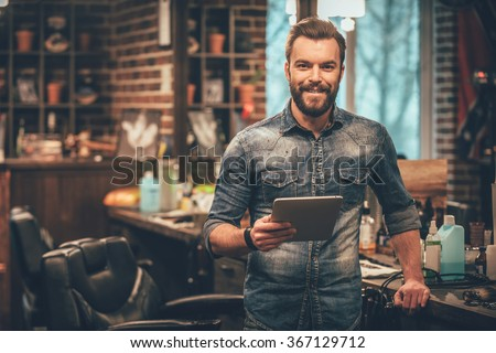 Keeping business on top with digital technologies. Cheerful young bearded man looking at camera and holding digital tablet while standing at barbershop Royalty-Free Stock Photo #367129712
