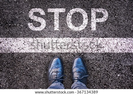Word Stop written on an asphalt road with legs and shoes Royalty-Free Stock Photo #367134389