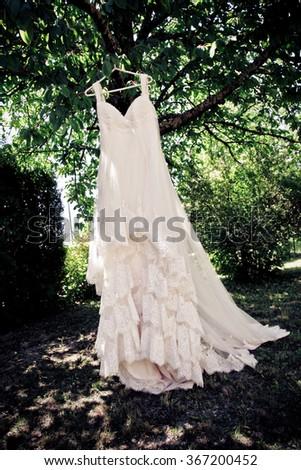 Wedding dress hanging on a tree #367200452
