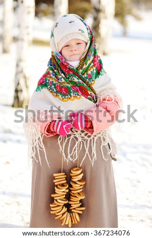 baby girl in Russian scarf on her head, and with a bunch of bagels on a background of snow and birches #367234076