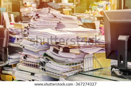 Pile of documents on desk stack up high waiting to be managed. Royalty-Free Stock Photo #367274327