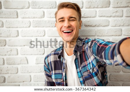 Beautiful young man in casual clothes make selfie on a background of white brick wall