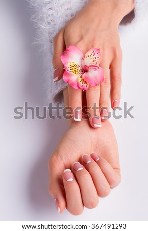 Beautiful pink freesia with franch moon manicure on a white background. #367491293