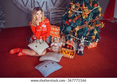 beautiful girl sits near decorated Christmas tree #367771166