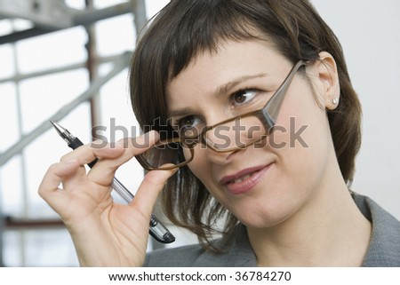 Businesswoman looking over eyeglasses with questions #36784270