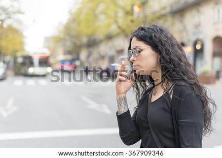 Smoking beautiful woman in the street. #367909346