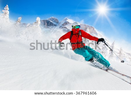 Skier skiing downhill during sunny day in high mountains #367961606