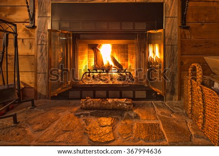 With the screen pulled back you can clearly see the warm fire in the stone fireplace.