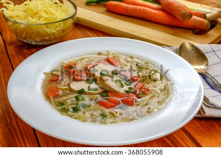 Traditional chicken soup with meat and carrot and noodles on wood table #368055908