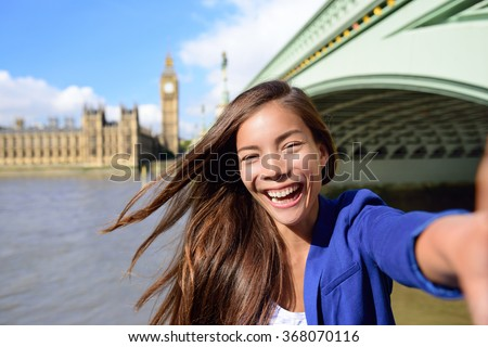 London travel selfie businesswoman. Joyful young casual business woman smiling at camera with Thames river, Big Ben and Westminster bridge background. Asian tourist using smartphone for picture.