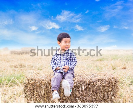 little beautiful boy sitting on a pile of hay in a field on a sunny day #368095397