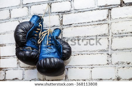 A pair of old blue and black boxing gloves hanging on white brick wall background.
