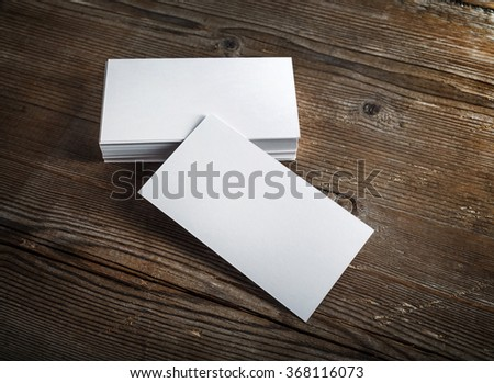 Blank white business cards on a dark wooden background. Mockup for branding identity. Blank template for design presentations and portfolios.