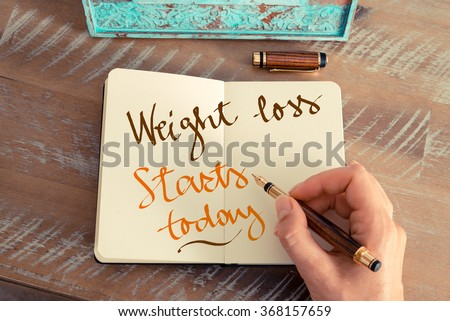 Retro effect and toned image of a woman hand writing a note with a fountain pen on a notebook. Handwritten text WEIGHT LOSS STARTS TODAY, motivation concept #368157659