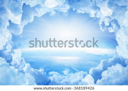 Light from heaven, blue planet Earth in white clouds, bright sunlight from above. Elements of this image furnished by NASA nasa.gov