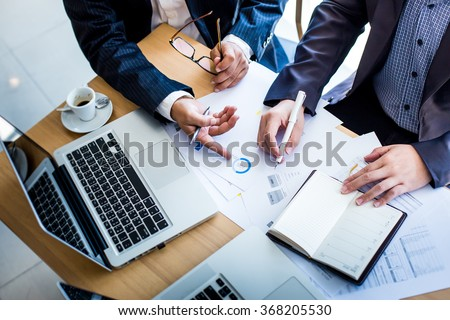 Business team hands at working with plan on office desk and modern digital computer laptop. Top view shot. Royalty-Free Stock Photo #368205530