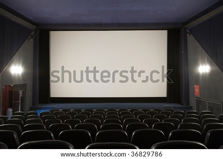 Empty cinema auditorium with line of chairs and stage with silver screen. Ready for adding your own picture. #36829786