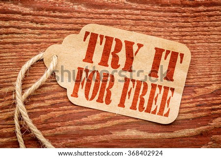 Try it for free  offer  - red stencil text on a paper price tag against rustic wood #368402924