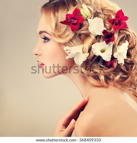 Beautiful girl, isolated on a light - grey background with varicoloured flowers in hairs, emotions, cosmetics #368409350
