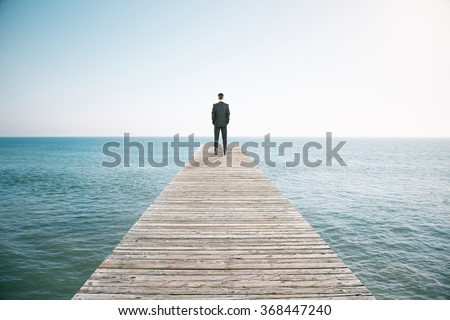 Man standing on the pier and looking into the distance of the ocean #368447240