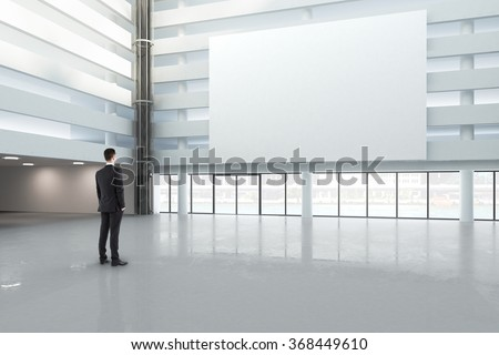 A man looking at a blank white banner in a large bright hall, mock up 3D Render
