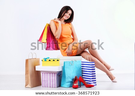 Beautiful young woman with shopping bags and boxes isolated on white #368571923
