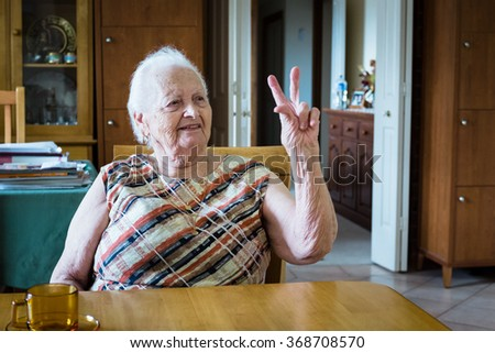 Old lady holding up two fingers and looking to right while sitting down at table #368708570