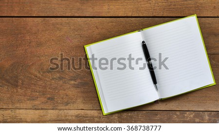 Top view workspace with blank notebook and pen on wooden table background . #368738777
