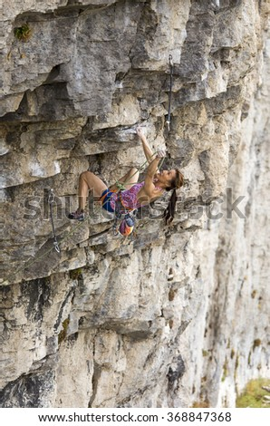 Female climber dangles from the edge of a challenging cliff. #368847368