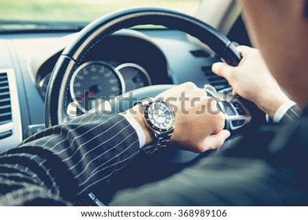 Man driving a car and looking at watch ,business concept ,vintage tone #368989106