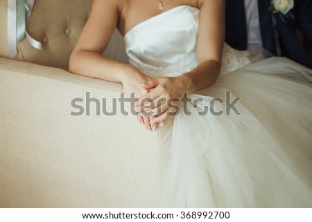 beautiful bride with manicure sitting on the couch, hands folded. #368992700