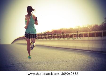 young fitness woman runner running on seaside bridge #369060662