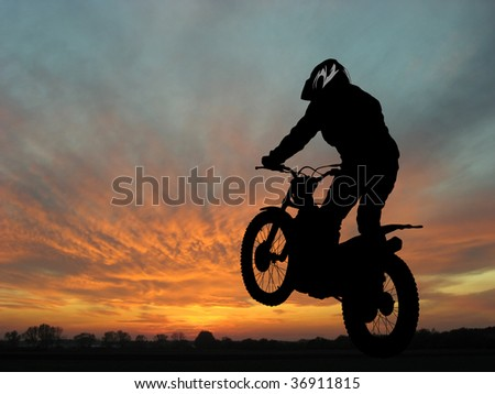 Silhouette of motorcyclist in sunset landscape
