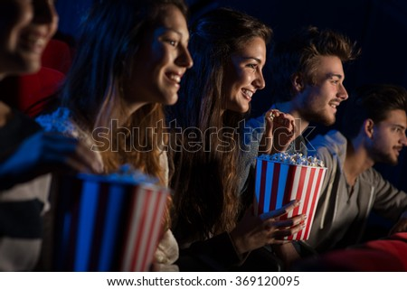 Group of teenager friends at the cinema watching a movie together and eating popcorn, entertainment and enjoyment concept #369120095
