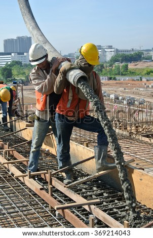 SELANGOR, MALAYSIA â?? MAY 2014: Construction workers are doing the concrete work using hose from the elephant crane or concrete pump crane on May 15, 2014 at Sepang, Malaysia.  #369214043