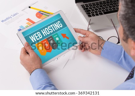 Man working on tablet with WEB HOSTING on a screen