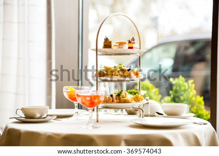 Beautiful english afternoon tea ceremony with desserts and snacks Royalty-Free Stock Photo #369574043