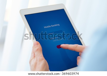 Male hands holds a tablet with online banking, login page on the touch screen #369603974
