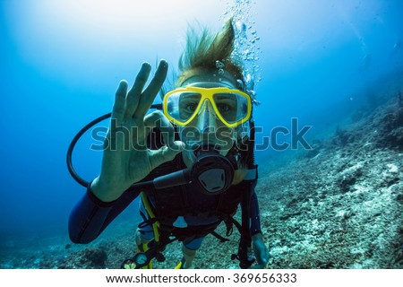 Lady scuba diver showing ok signal underwater Royalty-Free Stock Photo #369656333