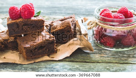 Chocolate brownies with raspberry on a wooden background #369667088