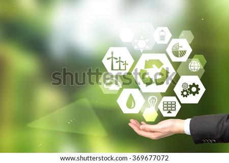 hand holding signs of different green sources of energy in hexahedron shape, a 'reduce, reuse, recycle' sign in the centre. Blurred green background. Concept of clean environment.