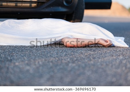 Body of a young child covered by a sheet lying on the street in front of the bumper of the car that ran him over with foreground copy space Royalty-Free Stock Photo #369696170