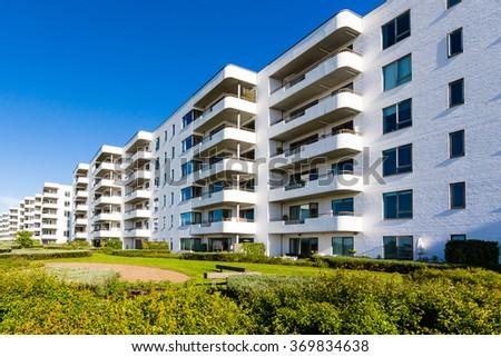 Modern white danish residential condominium building near Copenhagen, Denmark on a sunny day. #369834638