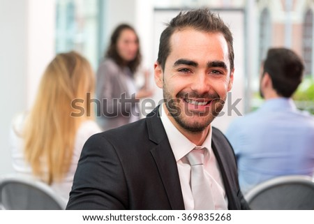 View of a Young attractive businessman working at the office with associates #369835268
