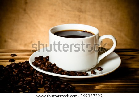Coffee beans and coffee in white cup on wooden table opposite a defocused burlap background. Toned. #369937322