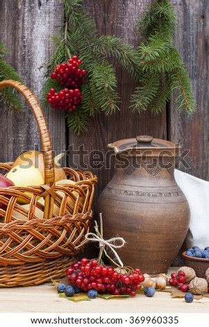 Autumn still life in Ukrainian style clay pot and autumn berry and vegetables on old wooden background, closeup #369960335
