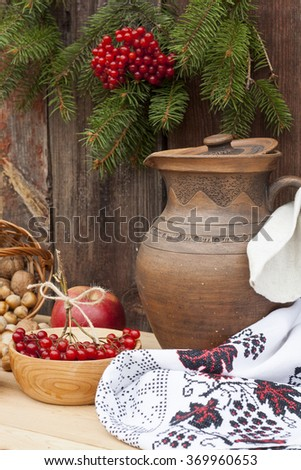 Autumn still life in Ukrainian style clay pot and autumn berry and vegetables on old wooden background, closeup #369960653