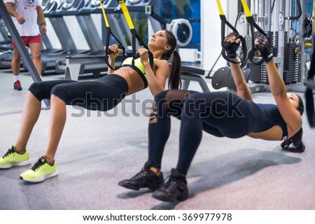 Woman exercising with suspension straps in fitness club or gym #369977978