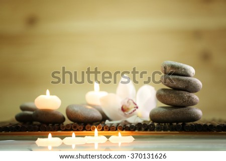 Spa still life with stones, candles and flowers in water on blurred background #370131626